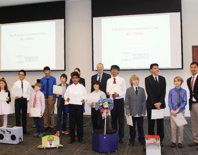 ENSCO President Boris Nejikovsky, back center, with members of the Robotics Inventors Club All Stars and their robots.